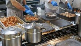 Concept de nourriture Le chef dans l'uniforme blanc surveille le degré de torréfaction et graisse la viande avec de l'huile dans  clips vidéos