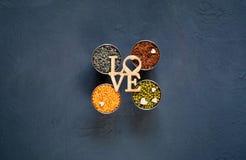 Concept de nourriture végétarienne Céréales et légumineuses avec l'inscription de l'amour sur un fond concret bleu Photographie stock libre de droits