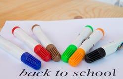 Concept de nouveau à l'école Feuille de papier avec le texte de nouveau à l'école et aux marqueurs colorés Photographie stock libre de droits