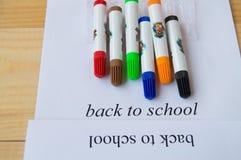 Concept de nouveau à l'école Feuille de papier avec le texte de nouveau à l'école et aux marqueurs colorés Photos stock