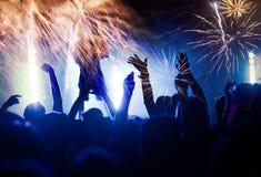 Concept de nouvelle année - foule et feux d'artifice encourageants Image stock