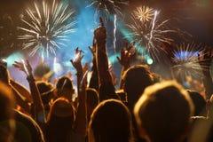 Concept de nouvelle année - foule et feux d'artifice encourageants Photos stock