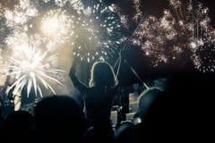 Concept de nouvelle année - foule et feux d'artifice encourageants Photographie stock