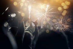Concept de nouvelle année - foule et feux d'artifice encourageants Photographie stock libre de droits