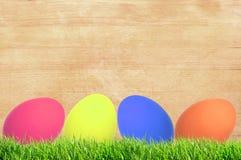 Concept de Pâques avec les oeufs colorés sur le fond en bois Image stock