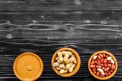 Concept de pâte d'arachide Les cuvettes avec du beurre, écrous dans la coquille, ont épluché des écrous sur l'espace en bois noir images stock