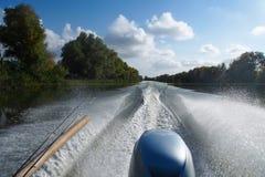 Concept de pêche Le bateau de pêche sur la rivière avec de l'eau les cannes à pêche et éclabousse Image libre de droits