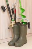 Concept de pêche : les cannes à pêche et la glace de main forent dedans les bottes en caoutchouc Images stock