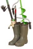 Concept de pêche : les cannes à pêche et la glace de main forent dedans les bottes en caoutchouc sur le fond blanc Photographie stock