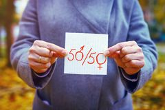 Concept de parité de genre la femme caucasienne de plan rapproché montre le papier avec le texte écrit cinquante avec des zéros e Image stock