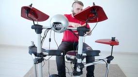 Concept de passe-temps et de musique Jeune homme ayant l'amusement jouant le tambour électronique Kit At Home banque de vidéos