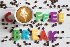 Concept de pause-café avec la tasse et le texte de café des lettres colorées sur les haricots rôtis photographie stock libre de droits