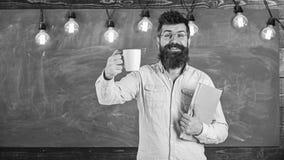 Concept de pause-café Homme avec la barbe sur le visage heureux dans la salle de classe Le professeur dans des lunettes tient le  photographie stock libre de droits