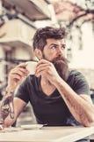 Concept de pause-café L'homme barbu tient la tasse d'expresso, boit du café à la terrasse L'homme avec la longue barbe semble rêv photos stock
