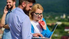 Concept de pause-café Les collègues payent l'ordinateur portable d'écran d'attention tandis que téléphone parlant d'homme Collègu photos libres de droits