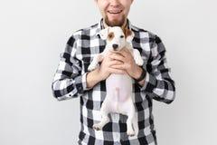 Concept de personnes, d'animaux familiers et de chiens - fermez-vous de l'homme étreignant le chiot drôle sur le fond blanc photos libres de droits