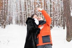 Concept de personnes, de saison, d'amour, de technologie et de loisirs - couple heureux prenant la photo avec le smartphone dessu Photos libres de droits