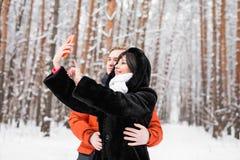 Concept de personnes, de saison, d'amour, de technologie et de loisirs - couple heureux prenant la photo avec le smartphone dessu Photo libre de droits
