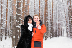 Concept de personnes, de saison, d'amour, de technologie et de loisirs - couple heureux prenant la photo avec le smartphone dessu Photographie stock