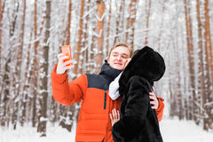 Concept de personnes, de saison, d'amour, de technologie et de loisirs - couple heureux prenant la photo avec le smartphone dessu Images stock