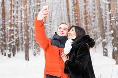 Concept de personnes, de saison, d'amour, de technologie et de loisirs - couple heureux prenant la photo avec le smartphone dessu Images libres de droits