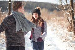 Concept de personnes, de saison, d'amour et de loisirs - couple heureux ayant l'amusement au-dessus du fond d'hiver Image stock