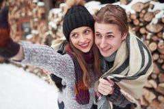 Concept de personnes, de saison, d'amour et de loisirs - couple heureux ayant l'amusement au-dessus du fond d'hiver Image libre de droits