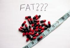 Concept de perte de poids avec de grosses pilules de brûleur et une bande de mesure Photos libres de droits