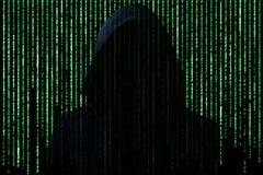 Concept de pirate informatique Personne méconnaissable dans les codes de caractère d'ordinateur de coupure de capot Photographie stock libre de droits