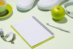 Concept de plan de forme physique Espadrilles, thé, pomme et écouteur dessus au delà Photographie stock