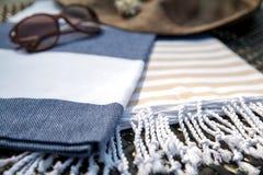 Concept de plan rapproché d'accessoires d'été de blanc, serviette turque beige et bleue, lunettes de soleil et chapeau de paille  Photo libre de droits
