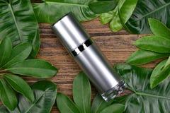 Concept de produit de beauté naturel de soins de la peau, récipients cosmétiques de bouteille sur le fond de fines herbes vert de Photo stock