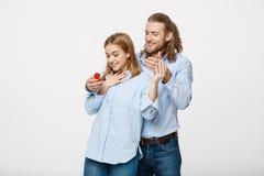 Concept de proposition - portrait de l'homme montrant un diamant de bague de fiançailles à sa belle amie au-dessus de blanc Photos stock