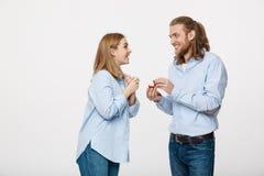 Concept de proposition - portrait de l'homme montrant un diamant de bague de fiançailles à sa belle amie au-dessus de blanc d'iso Image stock