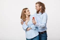 Concept de proposition - portrait de l'homme montrant un diamant de bague de fiançailles à sa belle amie au-dessus de blanc d'iso Images libres de droits