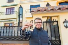 Concept de propriété, d'immobiliers, de propriété et de locataire - portrait d'une clé gaie de participation de jeune homme de no photographie stock libre de droits