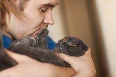 Concept de propriétaire et d'animal familier - le jeune homme tenant un écossais gris plient le chat en gros plan Image libre de droits