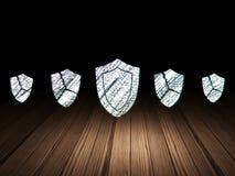 Concept de protection : icône de bouclier dans l'obscurité grunge Photos stock