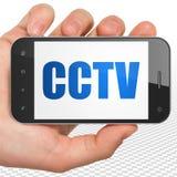 Concept de protection : Main tenant Smartphone avec la télévision en circuit fermé sur l'affichage Photos stock