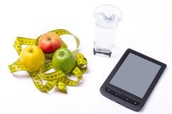 Concept de régime, de pommes fraîches et d'un verre de l'eau sur un Ba léger Photographie stock libre de droits
