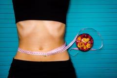 Concept de régime, de nutrition appropriée et de santé La fille mince mesure le ventre avec la bande de centimètre sur un fond en Images libres de droits