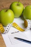 Concept de régime - papier avec le plan de régime, les pommes et la bande de mesure dessus Photos stock
