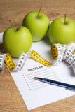 Concept de régime - papier avec le plan de régime, les pommes vertes et la mesure merci Photos libres de droits
