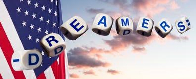 Concept de rêveurs utilisant des lettres d'orthographe contre le ciel et le drapeau de coucher du soleil photo stock