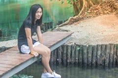 Concept de relaxation : Espadrille blanche d'usage de femme et se reposer sur le pont en bois au-dessus de la rivière Images libres de droits