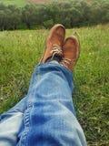 Concept de relaxation, jambes d'homme sur l'herbe pendant serein ensoleillé Photographie stock