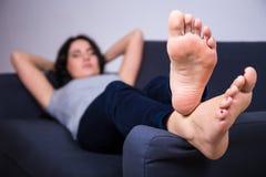 Concept de relaxation - jeune femme se trouvant sur le sofa à la maison image stock
