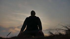 Concept de religion La silhouette d'un moine masculin s'est engag?e dans la m?ditation ? la lumi?re du soleil de coucher du solei clips vidéos