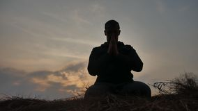Concept de religion Silhouette d'un moine masculin occupé dans le mode de vie de méditation à la lumière du soleil de coucher du  banque de vidéos