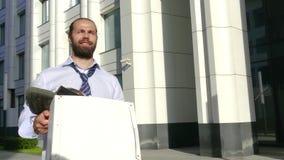 Concept de renvoi de travail, recrutement Un employé marche entre les immeubles de bureaux avec une boîte en carton et clips vidéos